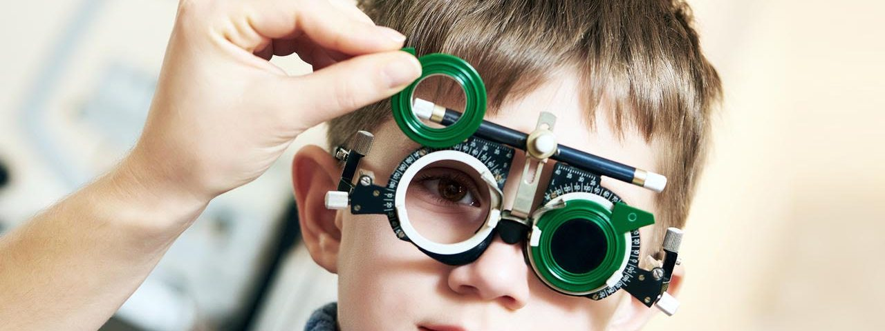boy getting an eye exam wearing green lenses